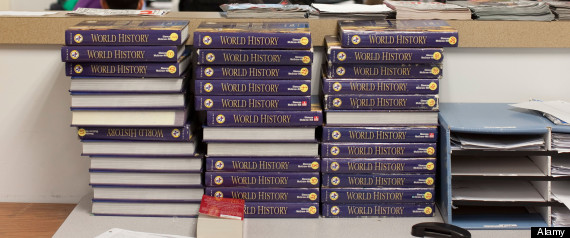 Unused world history books sit behind students in class at manor new