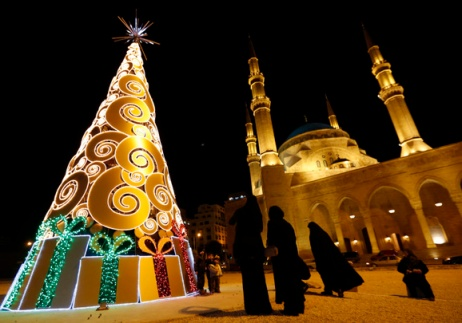 Residents stand near a Christmas tree in front of the Al-Amin mosque in downtown Beirut