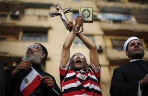 A protester holds a cross and Koran during a protest demanding that President Mohamed Mursi resign at Tahrir Square in Cairo