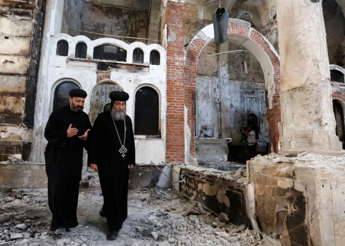 Bishop-General Macarius, a Coptic Orthodox leader, walks around the burnt and damaged Evangelical Church in Minya governorate