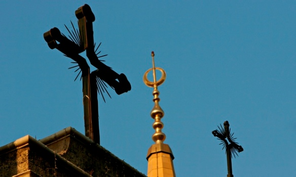 Mosque's minaret and cathedral's crosses