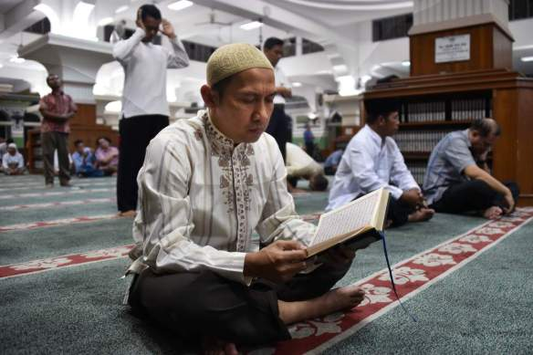 A man reads the koran as Indonesian Muslims wait for the first day of Ramadan prayers at Al-azhar Mosque in Jakarta on June 17, 2015, to mark the Muslim holy fasting month. More than 1.5 billion Muslims around the world will mark the month, during which believers abstain from eating, drinking, smoking and having sex from dawn until sunset. AFP PHOTO / Bay ISMOYO        (Photo credit should read BAY ISMOYO/AFP/Getty Images)