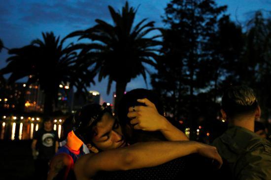Men hug during a vigil in a park following a mass shooting at the Pulse gay nightclub in Orlando Florida