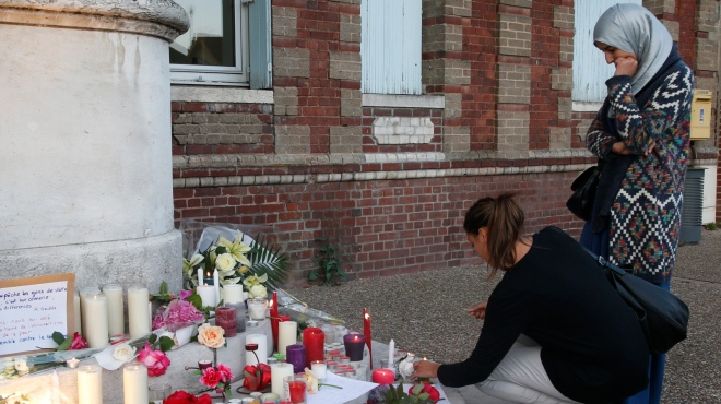 Women gather near flowers and candles at the city hall in Saint-Etienne-du-Rouvray to pay tribute to Father Jacques Hamel, who was killed in an attack on a church