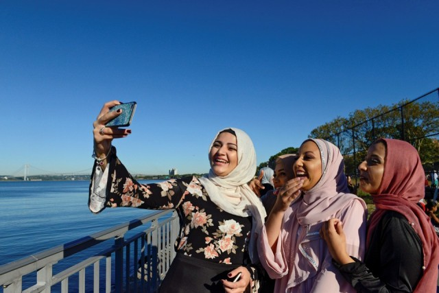 People take photos of each other before a group prayer session for the Muslim holiday Eid al-Adha in the Brooklyn borough of New York City