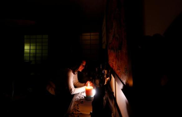 Ragaay prays and lights a candle in front of a wooden figure of Jesus in her home at the Cairo suburb of Maadi