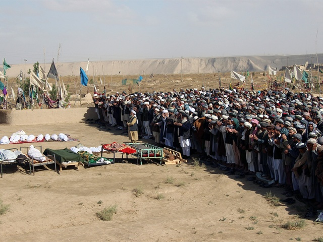 Afghans perform prayers at the funeral for the victims killed by an air strike called in to protect Afghan and U.S. forces during a raid on suspected Taliban militants, in Kunduz