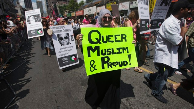 "Woman carrying a sign that reads, ""Queer, Muslim and Proud"" marches during the Gay Pride parade in Toronto"