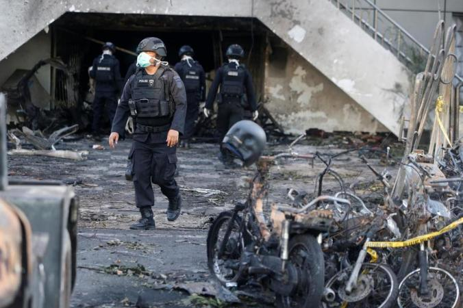 Indonesian Special Forces Police walks by burned motorcycles following a blast at GPPS in Surabaya