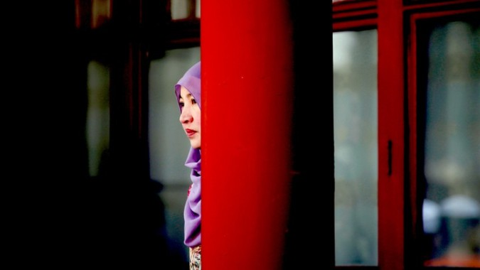 A woman stands behind a pillar during the Eid al-Adha festival at Niujie mosque in Beijing